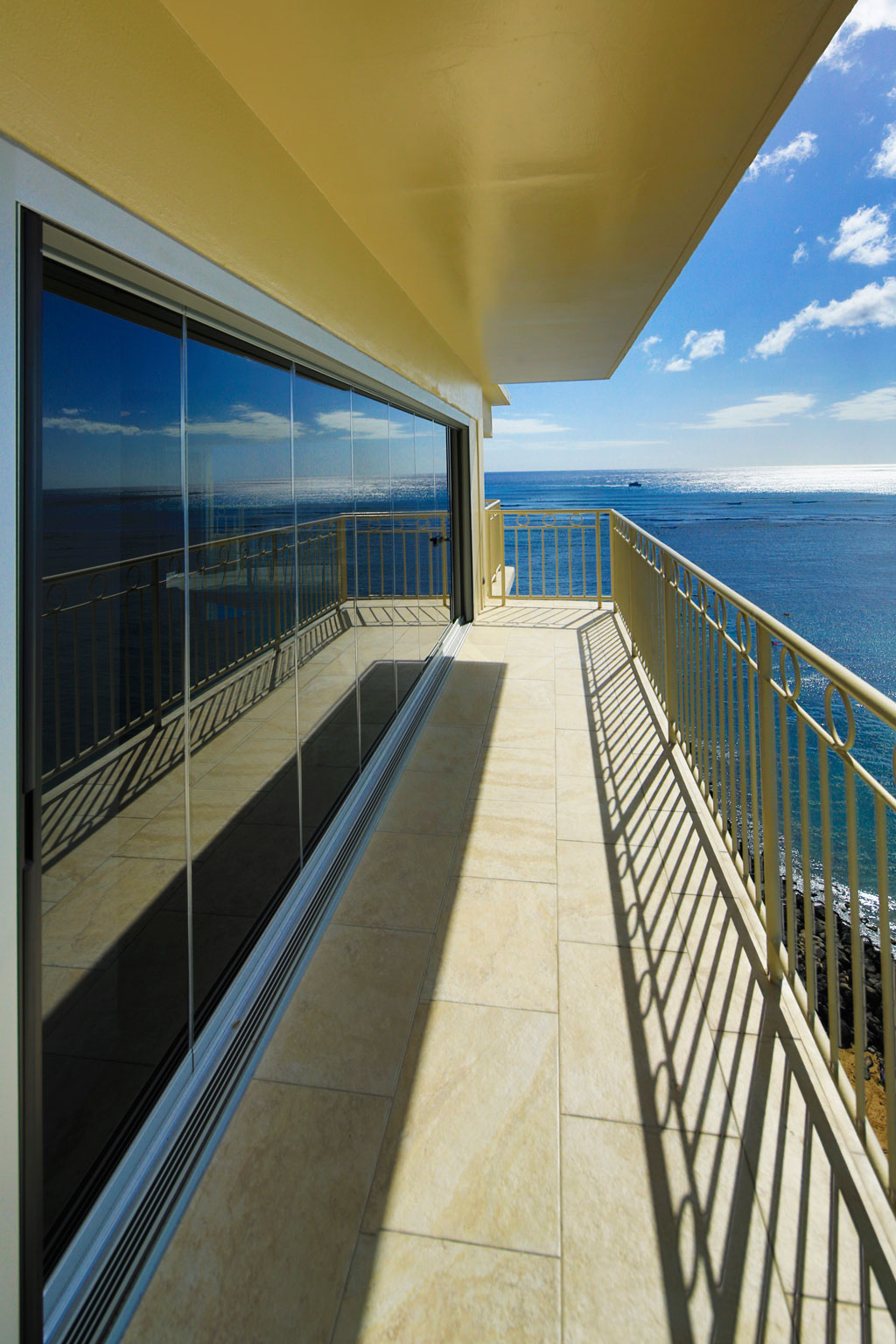 Custom grey glass 22 foot ocean front frameless sliding glass door withretractable Centor screens.